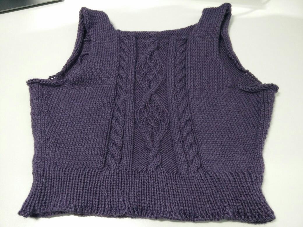 Photo d'un pull en cours de tricot, avec une grosse torsade triple au milieu du torse